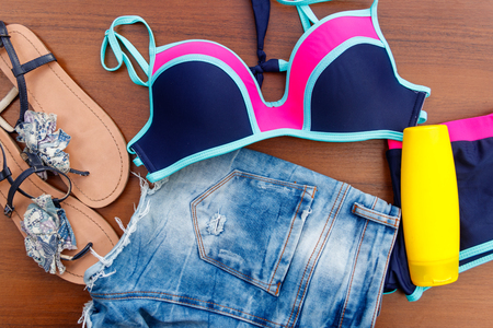 Photo for Set of beachwear on wooden background. Sunscreen, swimsuit, jean  shorts and flip-flops. Summer holiday concept - Royalty Free Image