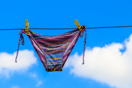 Photo for Drying female swimsuit hanging on a rope against blue sky. Summer vacation concept - Royalty Free Image