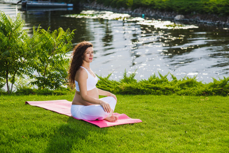 Photo for Woman sits in lotus position. - Royalty Free Image