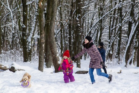 Photo for Family run in snow after their dog with purple toy - Royalty Free Image