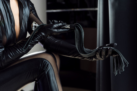 Foto de Black leather gloves and whip with fringe and handle. Mistress with a whip in room. - Imagen libre de derechos