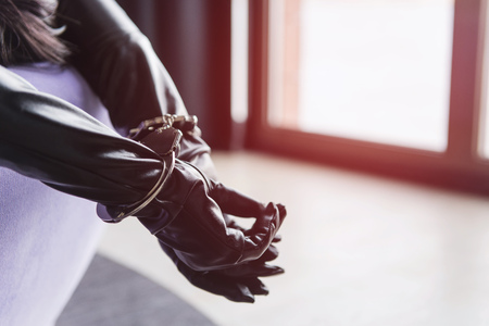 Foto de Woman in bed with hands in metal bracelets in sunset light. Female hands in leather gloves and handcuffs close-up. - Imagen libre de derechos