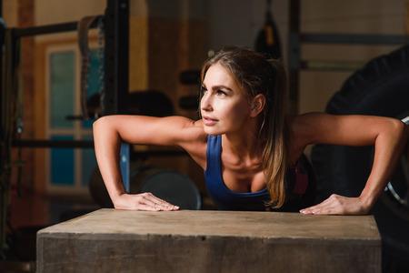 Photo pour Beautiful muscular woman doing exercise pushups - image libre de droit