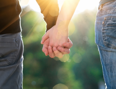 Concept shoot of friendship and love of man and woman: two hands over sun ray and nature