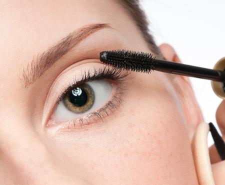 Beautiful woman applying mascara on her eyelashes - isolated on white