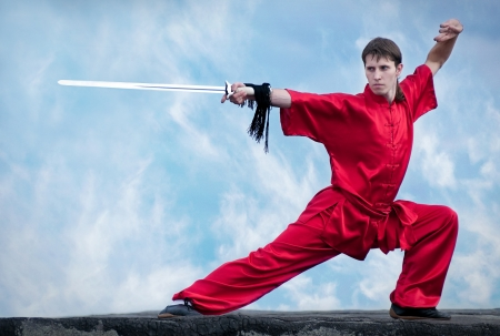 Shaolin warriors wushoo man in red with sword practice martial art outdoor. Kung fu