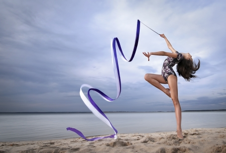 Photo pour young professional gymnast woman dance with ribbon - outdoor sand beach - image libre de droit