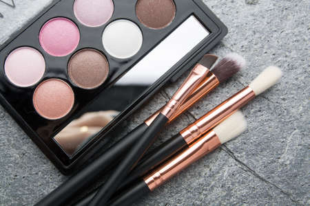 various makeup products on dark stone background
