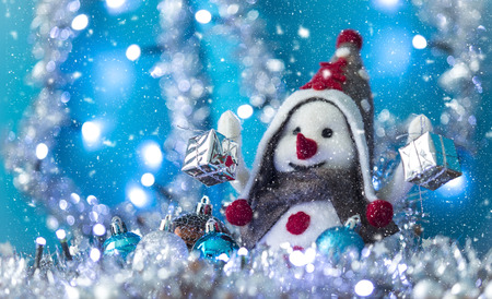 Snowman between Christmas balls smiling brought Christmas gifts, turquoise background with flashing lights snowing