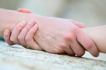 Foto de clasped hand for help on a granit rock - Imagen libre de derechos