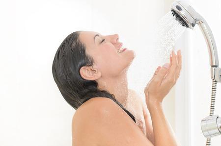 Photo pour Woman taking a shower enjoying water splashing on her - image libre de droit