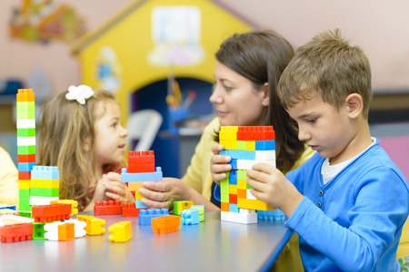 Photo pour Kids playing with plastic building blocks at kindergarten - image libre de droit