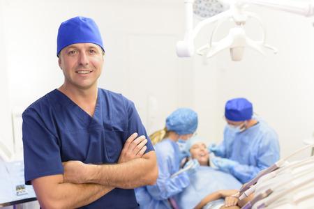Foto de Portrait of happy male dentist and his team at clinic - Imagen libre de derechos