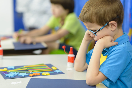 Photo pour Angry kid looking at his craft at kindergarten - image libre de droit