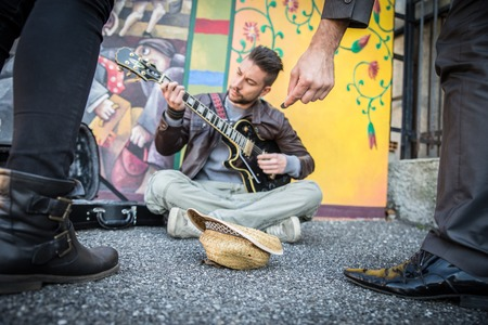Street artist peforming om the streets - People listening man playing guitar and giving charity