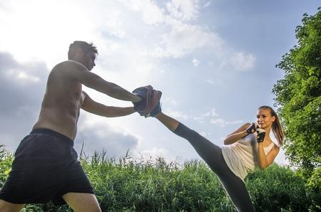Woman training  self difense martial arts with coach - Martial arts athlete kicks