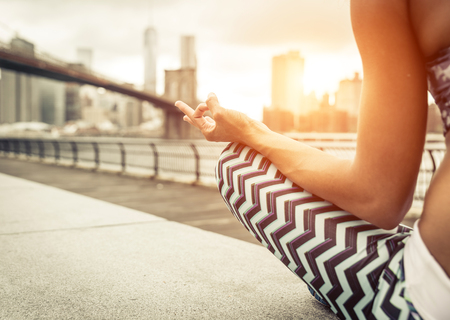 woman making yoga position in New york city at sunset time. Brooklyn bridge and new york skyline in the background