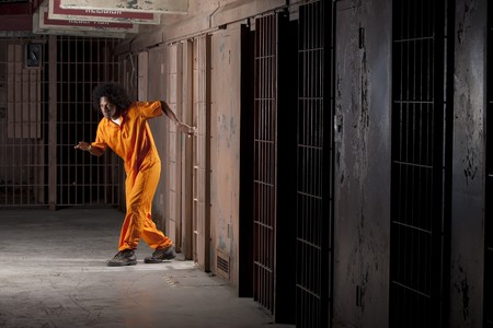 A young african american man with an afro is sneaking out of a prison cell. Vertical shot.