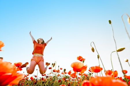 Photo for girl jumping in red poppies field - Royalty Free Image