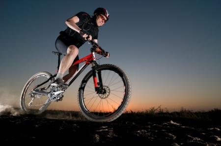 man extreme biking at sunset