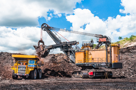 Foto de Electric rope shovels loading of coal, ore on the dump truck. The big dump truck is mining machinery, or mining equipment to transport coal from open-pit or open-cast mine as the Coal Production. - Imagen libre de derechos