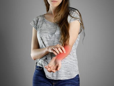 Foto de Girl in grey shirt scratching his arm. Scabies. Scratch the hand. Isolated. - Imagen libre de derechos