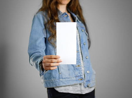 Photo pour The girl in the blue denim shirt holds the white empty piece of paper. Ready for your design. Closeup. Isolated. - image libre de droit