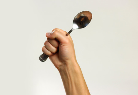 Photo for Male hands holding a metal tablespoon. Isolated on gray background. Closeup. - Royalty Free Image