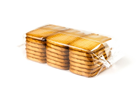 Foto de Golden cookies in a transparent package. Close up. Isolated on white background. - Imagen libre de derechos