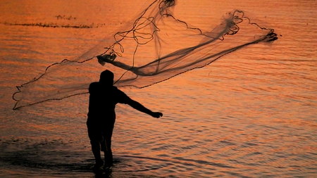 Foto de Silhouette of a fisherman casting fishing net  A fisherman casting a fishing net is silhouetted against the sunset island - Imagen libre de derechos