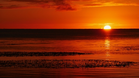 Photo pour A full round slowly disappears into the sea, Saipan Amazing sunsets in Saipan is a regular thing and one of the most outstanding features of the island. - image libre de droit