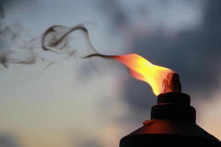 Foto de Fire and smoke rises from a lighted tiki torch - Imagen libre de derechos