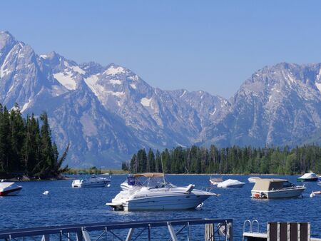 Photo pour Wyoming, USA- July 2018: Medium close up boats anchored at Colter Bay Village, with the snow-capped Grand Teton National Park mountain ranges in the background. - image libre de droit