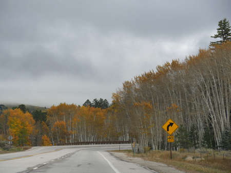 Photo pour Curved road bordered by colorful aspen trees up the mountains of Poncha Pass in south central Colorado. - image libre de droit