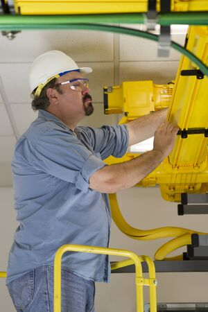 A telecommunication switch worker inspecting Fiberoptic cables in the fiberduct on a ladder platform. He is wearing hardhat and safety glasses. Surrounded by grounding telecom equipment cables.