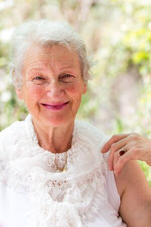 Photo for Grandmother still looking at you positively with her white hair and complimenting nice clothing. - Royalty Free Image