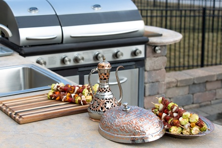 Photo for Skewers are in the traditional and authentic looking copper plate with complimenting pitcher. Meat skewers with vegetables at the outdoor kitchen on the concrete counter top. - Royalty Free Image