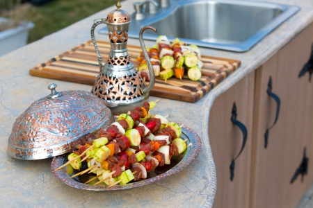 Photo for Raw skewers are waiting on the outdoor kitchen counter top. Skewers are in the copper plate  along with complimenting ornamented copper pitcher. - Royalty Free Image