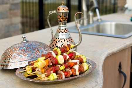 Photo for Raw meat and vegetable skewers are waiting on the outdoor kitchen counter top. Skewers are in the copper plate  along with complimenting ornamented copper pitcher. - Royalty Free Image