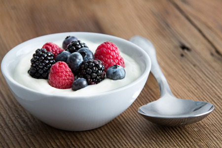 Photo for Bowl of fresh mixed berries and yogurt with farm fresh strawberries, blackberries and blueberries served on a wooden table - Royalty Free Image