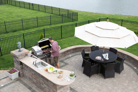 Photo pour High angle view of a man cooking meat on a gas BBQ standing in the sunshine on a paved outdoor patio at the summer kitchen preparing for guests with a table and chairs with a garden umbrella alongside - image libre de droit