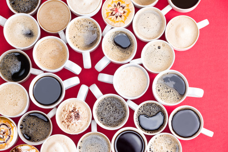 Photo pour Coffee mecca with multiple assorted types and flavors of coffee in identical white mugs artistically arranged with converging handles in the centre on a red background, overhead view - image libre de droit