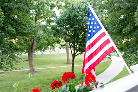 American Stars and Stripes flag flying from a balcony or patio overlooking a park with trees in a patriotic gesture or to celebrate the 4th July and Independence Day