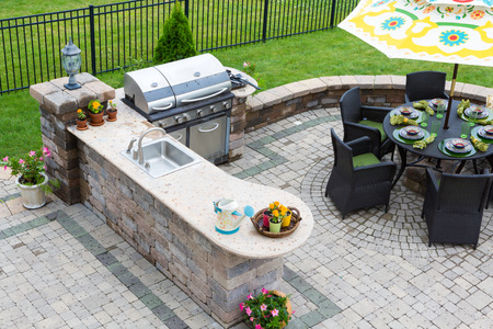 Foto de stylish outdoor kitchen, gas barbecue and dining table set for entertaining guests with formal place settings and flowers on a paved patio - Imagen libre de derechos
