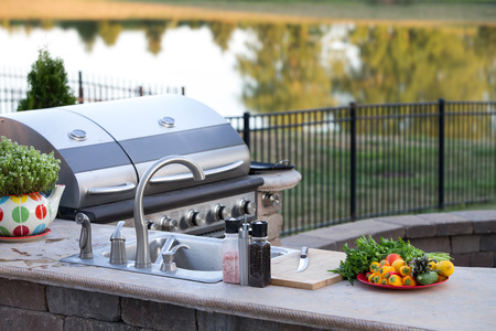 Photo pour Preparing a healthy summer meal in an outdoor kitchen with gas barbecue and sink on a brick patio overlooking a tranquil lake with tree reflections - image libre de droit