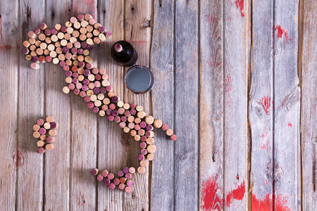 Photo pour Artistic conceptual map of Italy, Sardinia and Sicily made of old red and white wine bottle corks on an old rustic wooden table with a glass and bottle of red wine alongside - image libre de droit