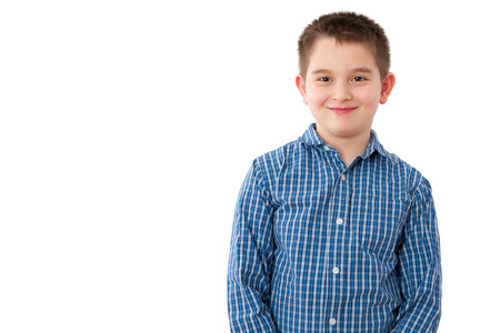 Photo for Portrait of a Cute 10 Year Old Boy with a Mischievous Sweet Smile, Standing Against White Background with Copy Space. - Royalty Free Image