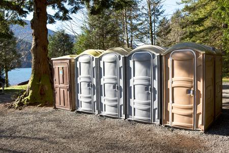 Foto de Portapotty, or portable enclosed plastic portable toilet with chemicals and deodorizers in a tank, in a park yard for public convenience - Imagen libre de derechos