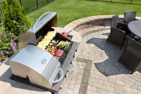 Foto de Grilling healthy food with corn, kebabs, meat and sausages on an outdoor gas barbecue on a luxury brick paved patio and summer kitchen in a neatly manicured back yard - Imagen libre de derechos