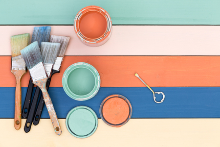 Foto de Colorful multicolored stained wood background in pastel shades with painting supplies of opened tins of stain and clean paintbrushes with copy space, overhead view - Imagen libre de derechos